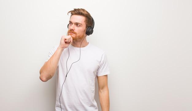 Jeune homme rousse doutant et confus. écouter de la musique avec des écouteurs.