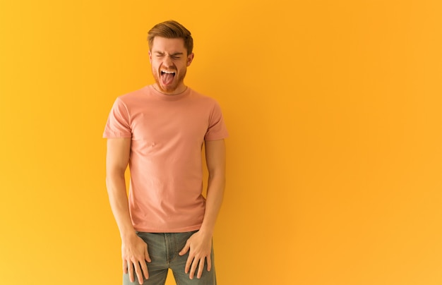 Jeune homme rousse drôle et amical montrant la langue