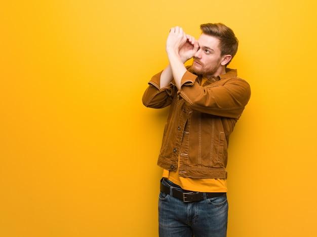 Jeune homme rousse faisant le geste d'une longue-vue