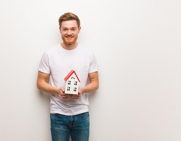 Jeune homme rousse gai avec un grand sourire. tenant un modèle de maison.