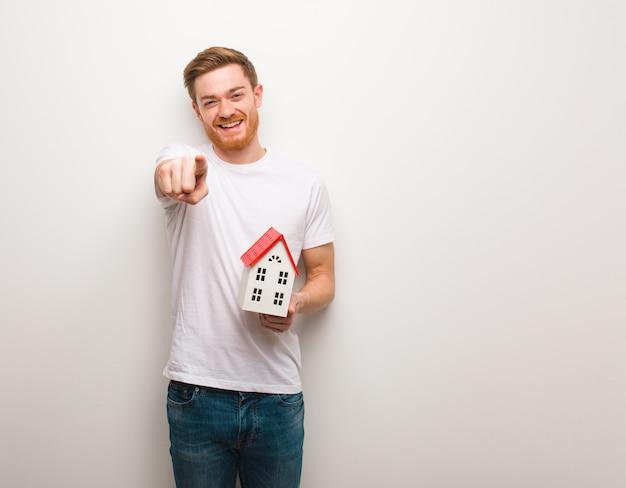 Jeune homme rousse gai et souriant pointant vers l'avant. tenant un modèle de maison.