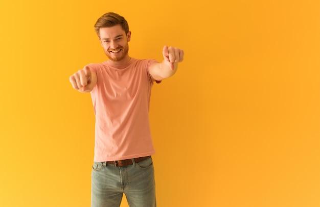 Jeune homme rousse gai et souriant pointant vers l'avant