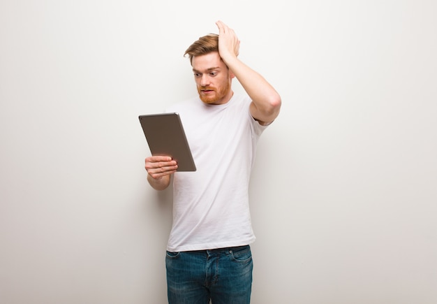 Jeune homme rousse inquiet et dépassé et tenant une tablette