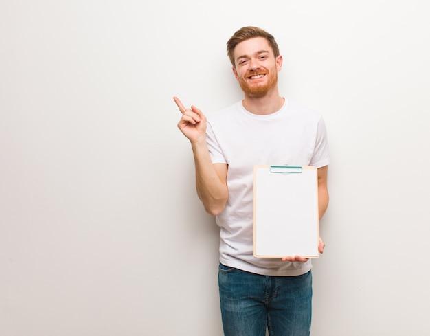 Jeune homme rousse pointant sur le côté avec le doigt. il tient un presse-papiers.