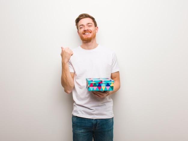 Jeune homme rousse pointant sur le côté avec le doigt. tenir une boîte cadeau.