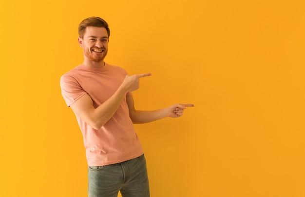 Jeune homme rousse pointant sur le côté avec le doigt