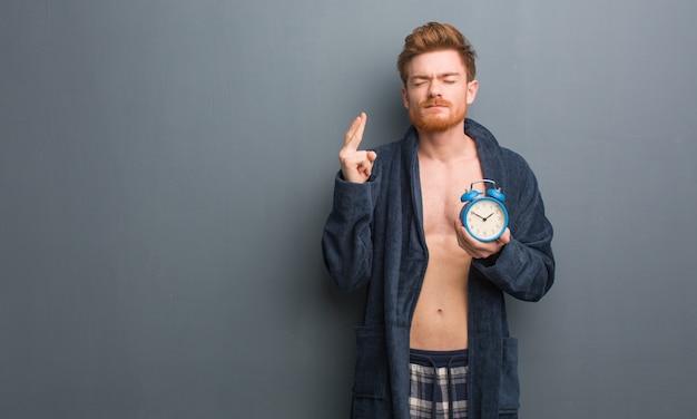 Jeune homme rousse portant les doigts croisés en pyjama pour avoir de la chance. il tient un réveil.