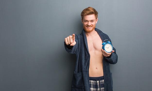 Jeune homme rousse portant un pyjama joyeux et souriant pointant vers l'avant. il tient un réveil.