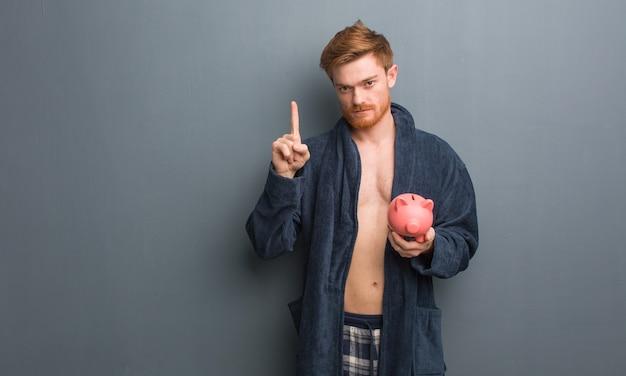 Jeune homme rousse portant un pyjama montrant le numéro un. il tient une tirelire.