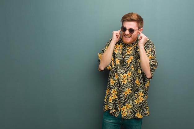 Jeune homme rousse portant des vêtements d'été exotiques couvrant les oreilles avec les mains