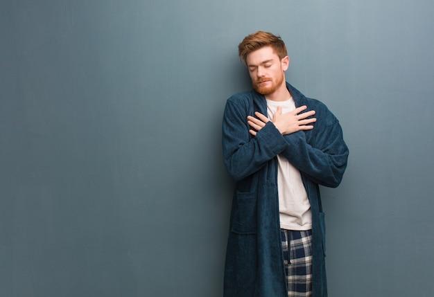 Jeune homme rousse en pyjama donnant un câlin