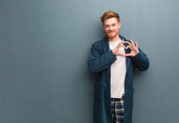 Jeune homme rousse en pyjama faisant une forme de coeur avec les mains