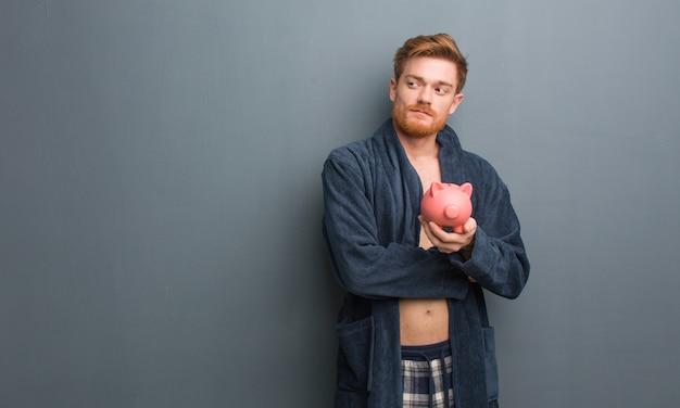 Jeune homme rousse en pyjama souriant, confiant et bras croisés, levant les yeux. il tient une tirelire.