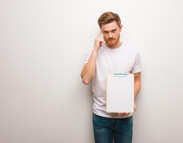 Jeune homme rousse réfléchissant à une idée. il tient un presse-papiers.