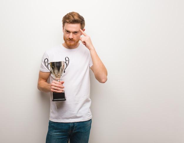Jeune homme rousse réfléchissant à une idée. tenant un trophée.