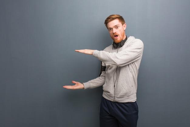 Jeune homme rousse de remise en forme tenant quelque chose de très surpris et choqué