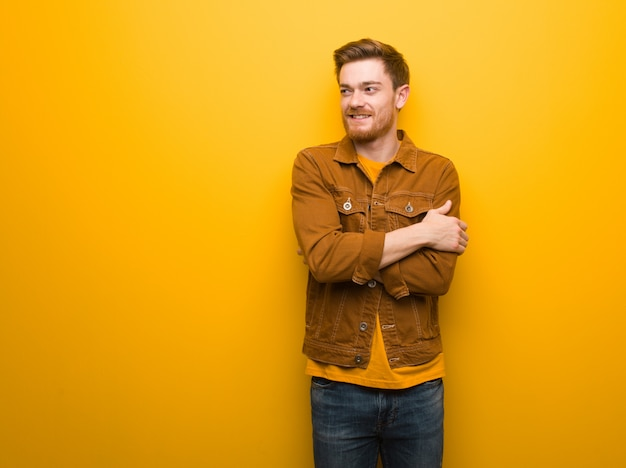 Jeune homme rousse souriant confiant et croisant les bras, levant