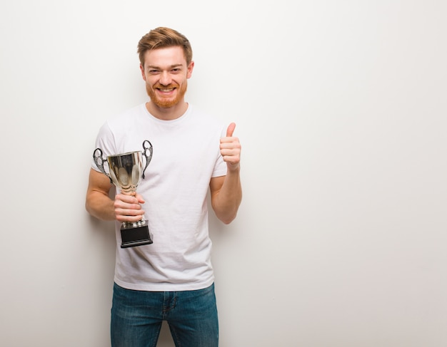 Jeune homme rousse souriant et levant le pouce vers le haut. tenant un trophée.