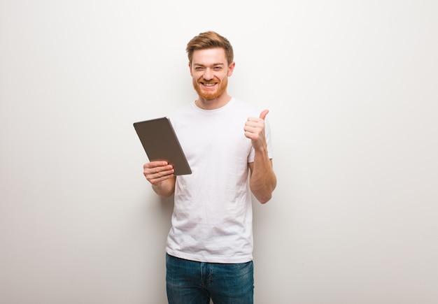 Jeune homme rousse souriant et levant le pouce vers le haut