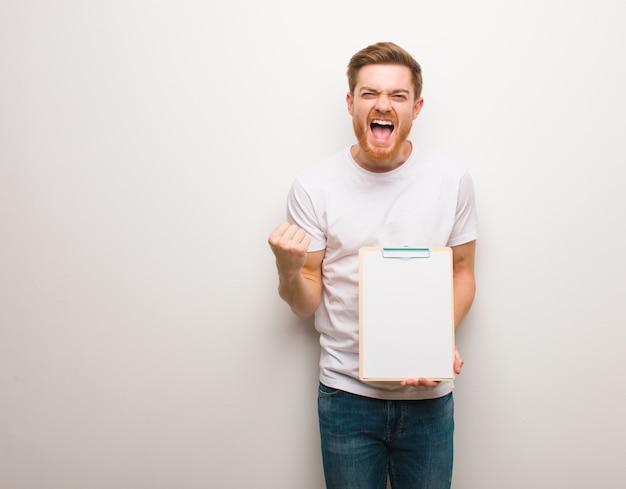 Jeune homme rousse surpris et choqué. il tient un presse-papiers.