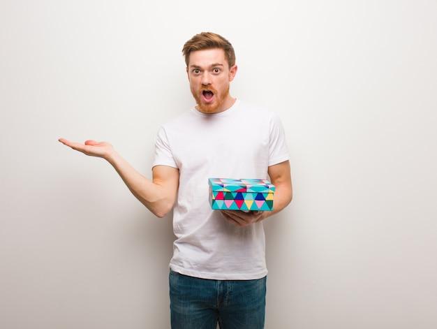 Jeune homme rousse tenant quelque chose sur la main de la paume. tenant une boîte cadeau.