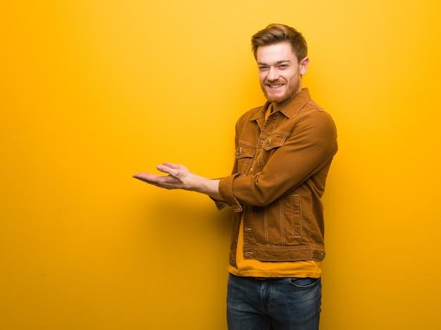 Jeune homme rousse tenant quelque chose avec les mains