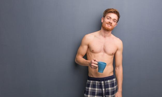 Jeune homme rousse torse nu gai avec un grand sourire