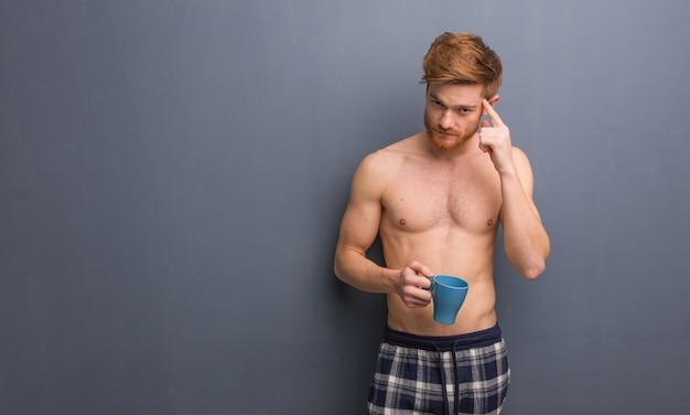 Jeune homme rousse torse nu réfléchissant à une idée. il tient une tasse de café.