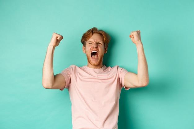 Jeune homme rousse triomphant en regardant un match de sport, faisant le pari sur l'équipe gagnante et se réjouissant, criant de joie et de satisfaction, debout sur fond turquoise.