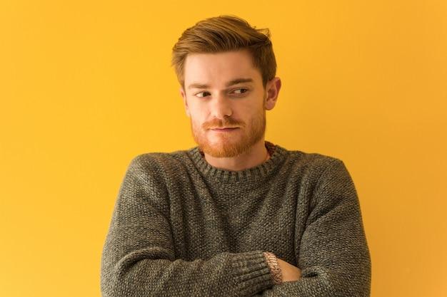 Jeune homme rousse visage closeup souriant confiant et bras croisés, levant