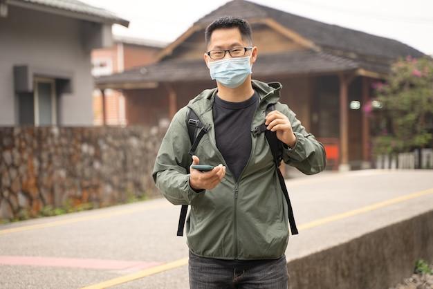Un jeune homme routard voyage seul et utilise un téléphone intelligent pour trouver un moyen de porter un masque, des lunettes