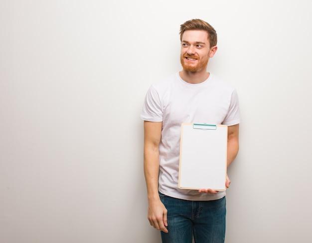 Jeune homme roux souriant confiant et croisant les bras, levant les yeux. il tient un presse-papiers.