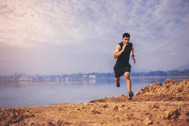 Jeune homme runner running trail sur le lever du soleil au bord du lac concept sain et mode de vie
