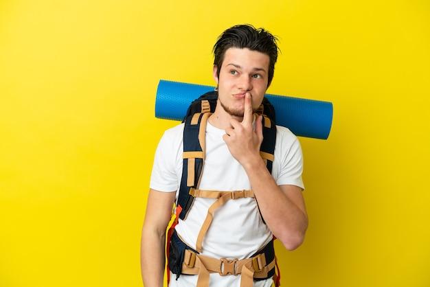 Jeune homme russe d'alpiniste avec un grand sac à dos d'isolement sur le fond jaune ayant des doutes tout en levant