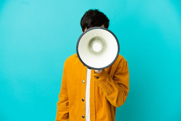 Jeune homme russe isolé sur fond bleu criant à travers un mégaphone pour annoncer quelque chose