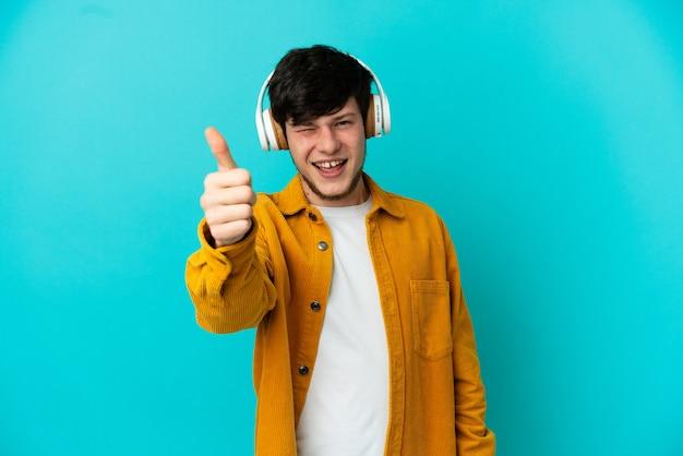 Jeune homme russe isolé sur fond bleu, écouter de la musique et avec le pouce vers le haut