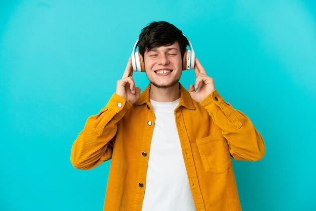 Jeune homme russe isolé sur fond bleu, écouter de la musique