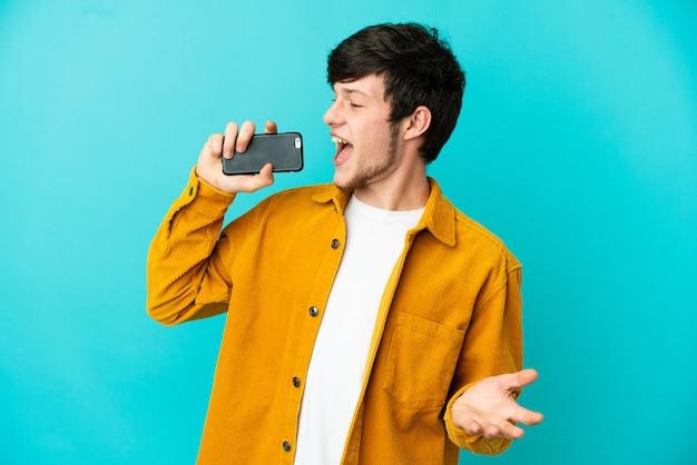 Jeune homme russe isolé sur fond bleu utilisant un téléphone portable et chantant