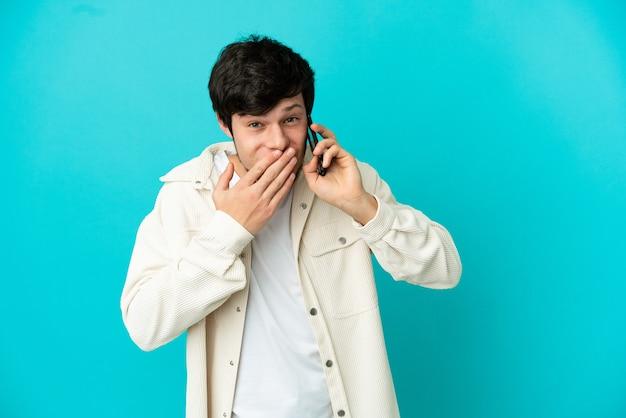 Jeune homme russe utilisant un téléphone portable isolé sur fond bleu heureux et souriant couvrant la bouche avec la main