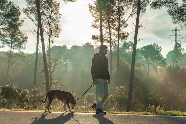 Jeune homme s'amusant avec son chien dans la nature avec les rayons du soleil du matin aime mon chien