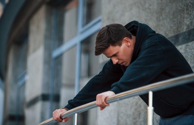 Jeune homme s'appuyant sur les balustrades de couleur argent. se sent fatigué.