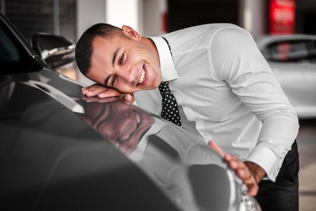 Jeune homme s'appuyant sur une voiture neuve