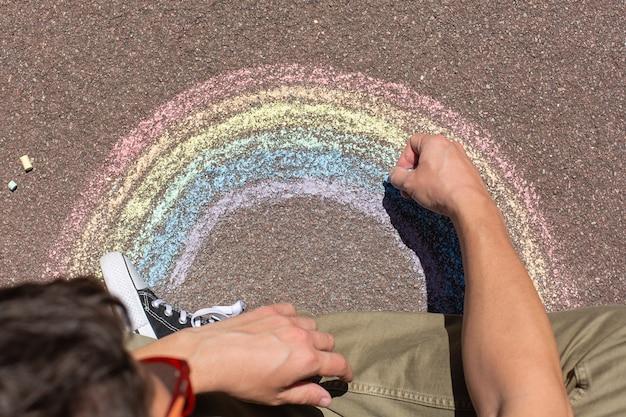Le jeune homme s'assied sur un trottoir et dessine l'arc-en-ciel
