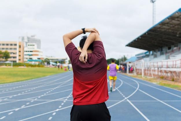 Jeune homme s'échauffe avant de courir. concept d'exercice. concept d'échauffement. concept d'entraînement