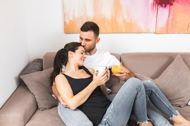 Jeune homme s'embrasser sur la tête de son petit ami tenant une tasse de café et un verre de jus