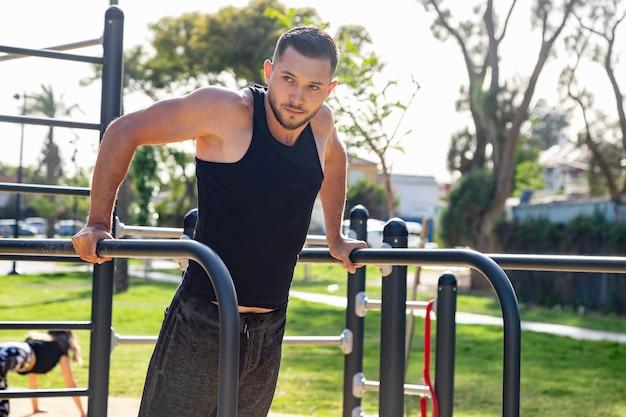 Un jeune homme s'entraîne sur le terrain de sport