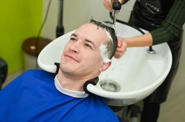 Le jeune homme s'est coupé les cheveux chez le coiffeur. coupe chez le coiffeur. salon de coiffure