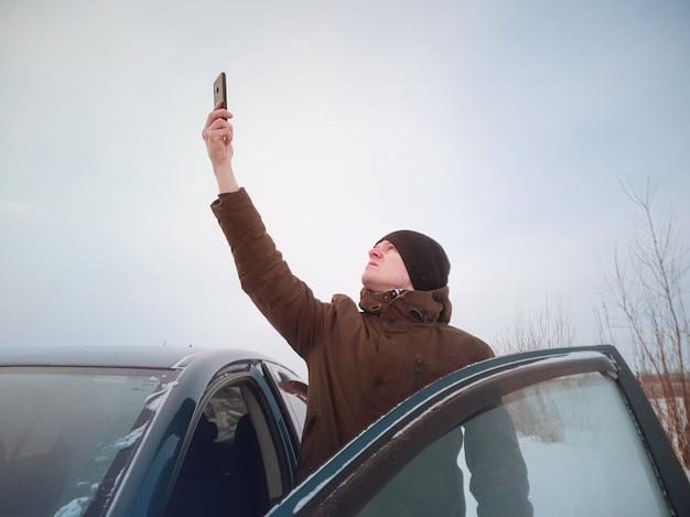 Un jeune homme s'est perdu dans une voiture en hiver et tente d'attraper le réseau mobile après être sorti de la voiture. concept de route d'hiver, recherche de route, navigation.