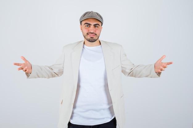 Jeune homme s'étirant les mains de manière interrogative en t-shirt blanc, veste et casquette grise et l'air heureux