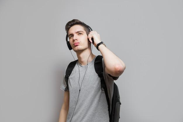 Jeune homme avec un sac à dos dans les écouteurs sur fond gris. un étudiant avec un sac écoute de la musique.